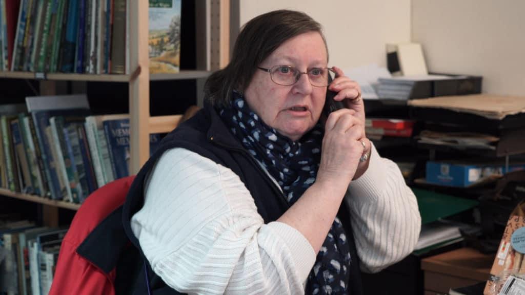 Volunteer on phone in boat museum